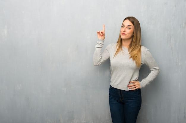 Jonge vrouw op geweven muur die en een vinger in teken van het beste toont opheft Premium Foto