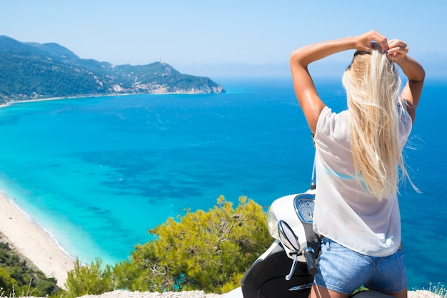 Jonge vrouw op motorfiets aan zee genieten van het uitzicht op het strand Gratis Foto