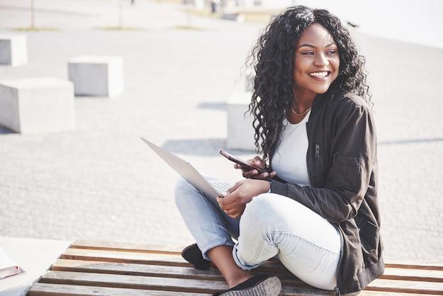 Jonge vrouw op straat die aan laptop werkt en op mobiele telefoon spreekt Premium Foto