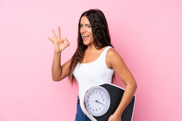 Jonge vrouw over geïsoleerd roze die een weegmachine houdt en ok teken doet Premium Foto