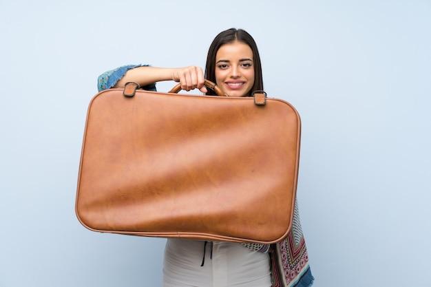 Jonge vrouw over geïsoleerde blauwe muur die een uitstekende aktentas houdt Premium Foto