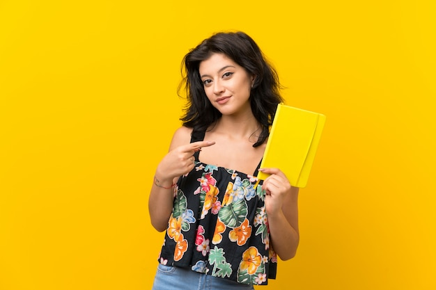 Jonge vrouw over geïsoleerde gele muur die en een boek houdt leest Premium Foto