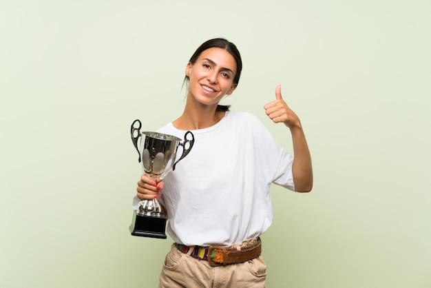 Jonge vrouw over geïsoleerde groene muur die een trofee houdt Premium Foto