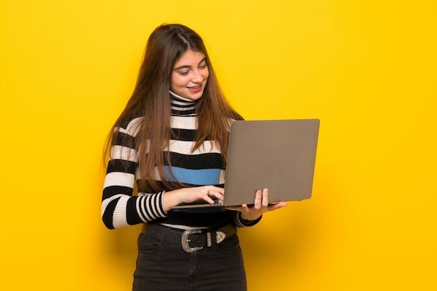 Jonge vrouw over gele muur met laptop Premium Foto