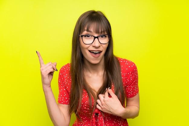Jonge vrouw over groene muur met verrassing gelaatsuitdrukking Premium Foto