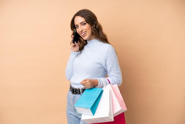 Jonge vrouw over muur boodschappentassen houden en een vriend bellen met haar mobiele telefoon Premium Foto