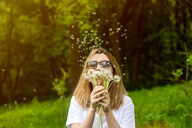 Jonge vrouw paardebloem in de zomerpark blazen. Premium Foto