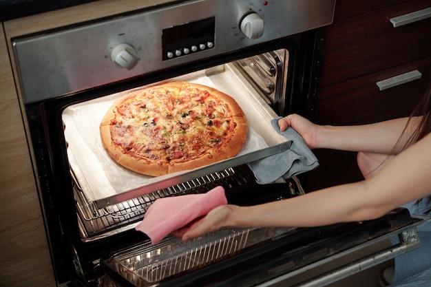 Jonge vrouw pizza koken Premium Foto