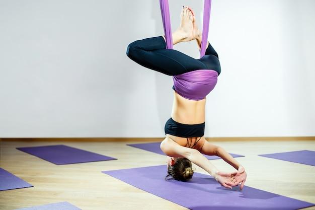 Jonge vrouw poseren doen luchtfoto yoga-oefening met hangmat Premium Foto