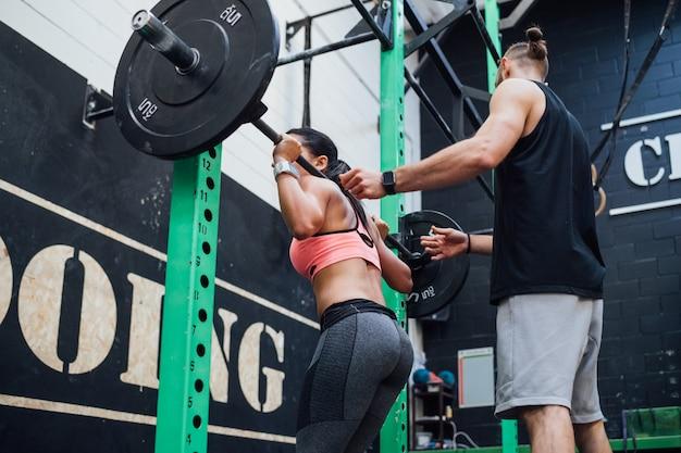 Jonge vrouw power tillen geholpen door haar persoonlijke trainer Premium Foto