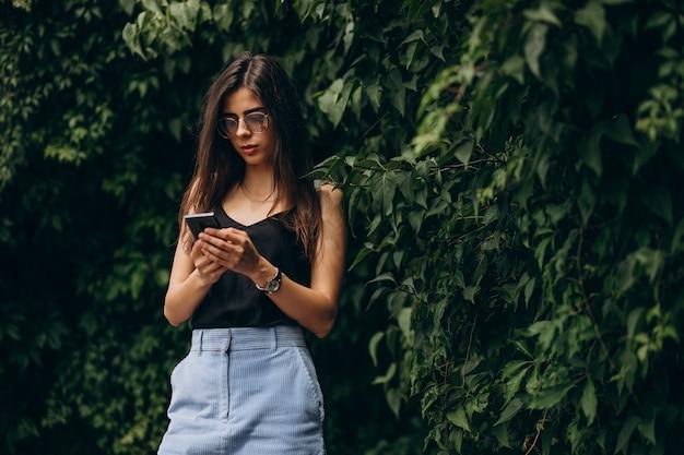 Jonge vrouw praten over de telefoon in park Gratis Foto