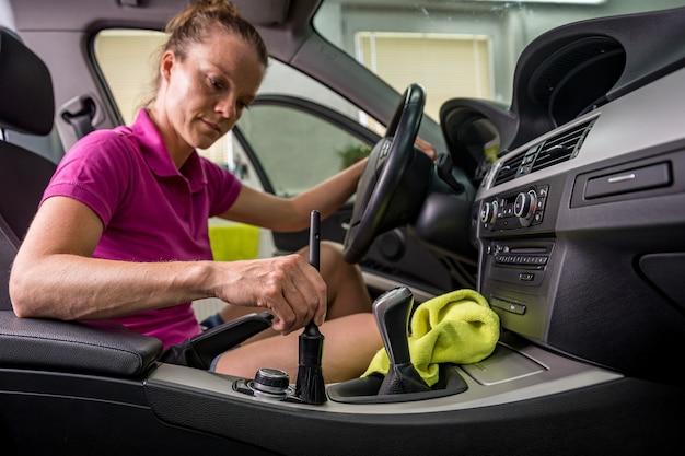 Jonge vrouw reinigt het interieur van het voertuig Premium Foto