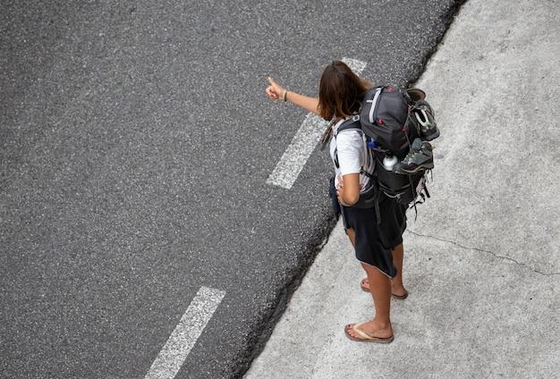 Jonge vrouw reist liftend in de buurt van een weg Premium Foto