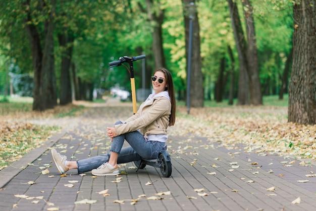 Jonge vrouw rijdt op een elektrische scooter in een herfstpark. groen vervoer, fileproblemen. Premium Foto