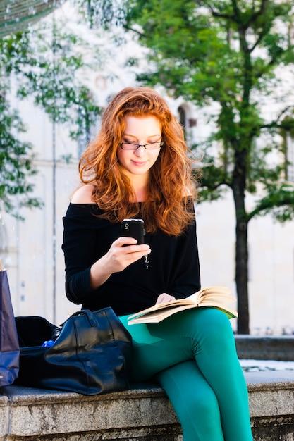Jonge vrouw roept met mobiele telefoon in het park Premium Foto