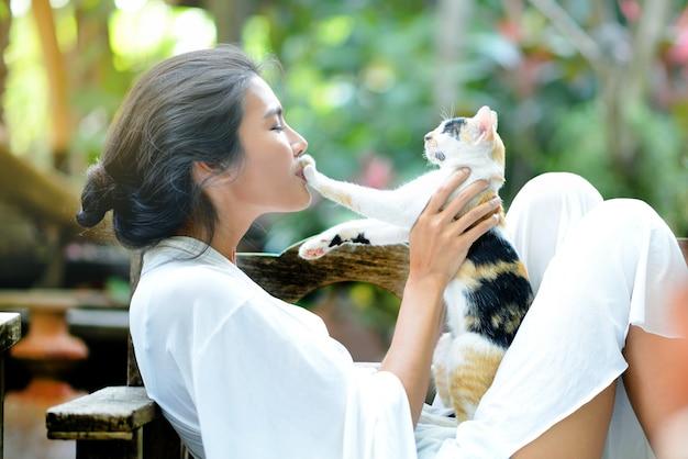 Jonge vrouw rust met een kat op de fauteuil in de tuin Premium Foto