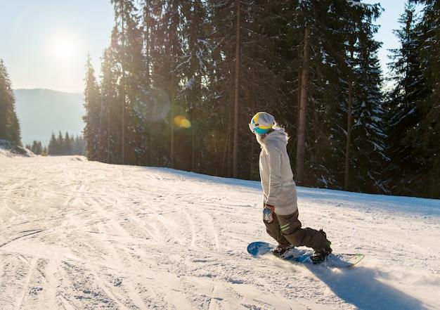 Jonge vrouw snowboarden op de helling op een mooie zonnige winteravond Premium Foto