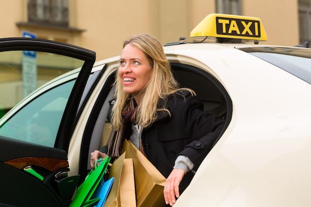 Jonge vrouw stapt uit de taxi Premium Foto
