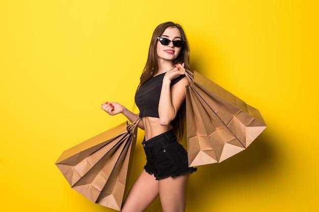 Jonge vrouw status geïsoleerd over gele muurholding het winkelen zakken Gratis Foto