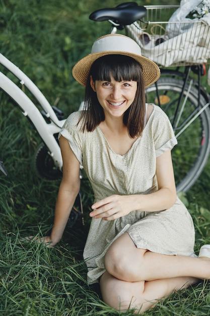 Jonge vrouw tegen aardachtergrond met fiets Gratis Foto