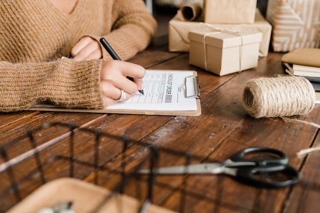 Jonge vrouw teken zetten door bestelde goederen in controlelijst zittend door houten tafel onder verpakte dozen Premium Foto