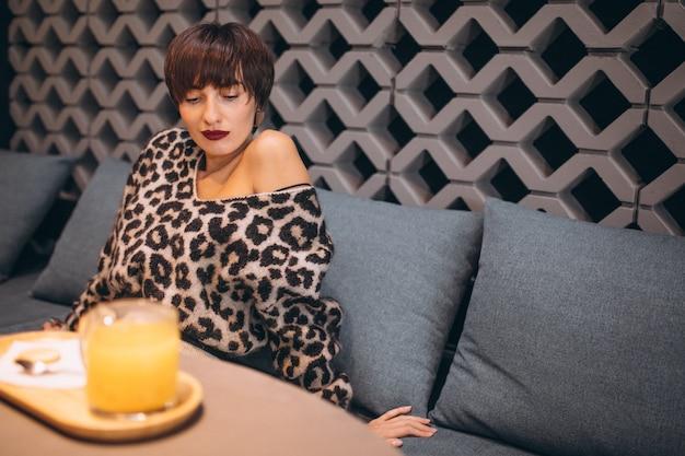 Jonge vrouw thee drinken in een café Gratis Foto