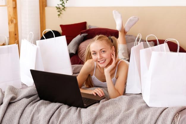 Jonge vrouw thuis met laptop en witte papieren zakken Premium Foto