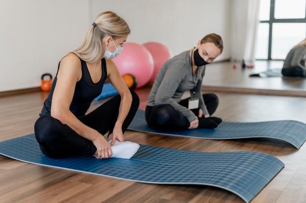 Jonge vrouw trainen in de sportschool en coach op yogamatten Gratis Foto