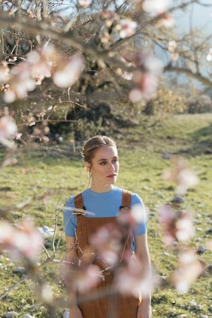 Jonge vrouw tussen bloeiende takken Gratis Foto