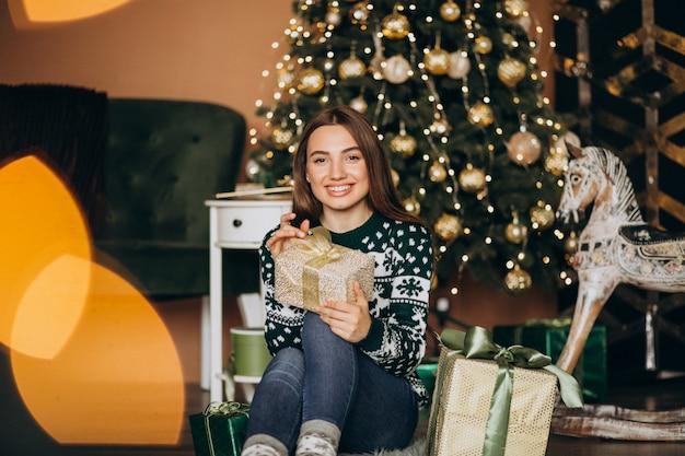 Jonge vrouw uitpakken kerstcadeau door de kerstboom Gratis Foto