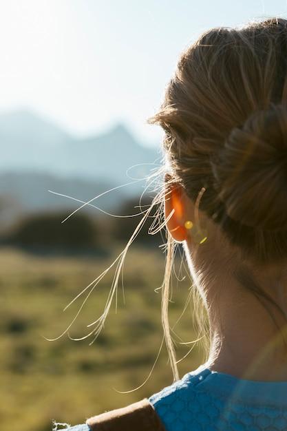 Jonge vrouw van achter onder ogen ziende zon Gratis Foto