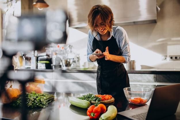 Jonge vrouw videoblogger koken in de keuken en filmen Gratis Foto