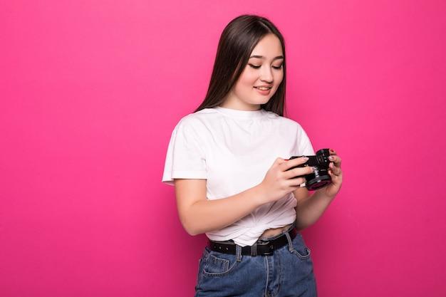 Jonge vrouw vrolijk met fotocamera op roze muur Gratis Foto