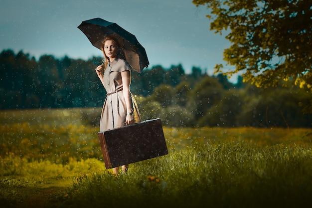 Jonge vrouw weglopen met een koffer onder regen Premium Foto