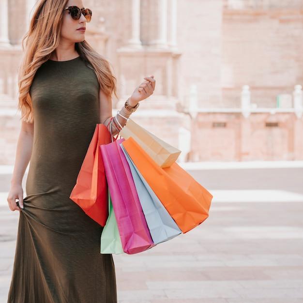 Jonge vrouw winkelen in de stad Gratis Foto