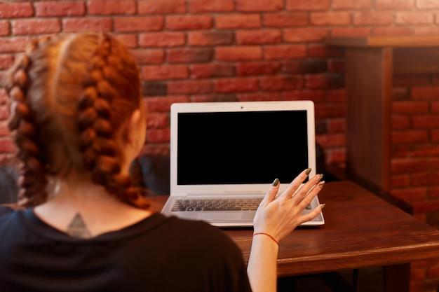 Jonge vrouw zit in café met laptop Gratis Foto
