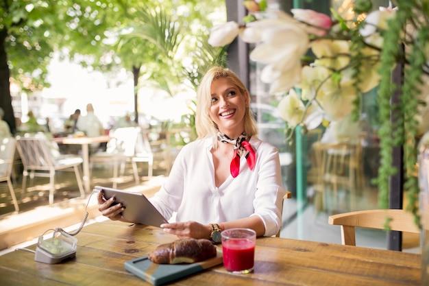 Jonge vrouw zitten in café met behulp van digitale tablet Gratis Foto