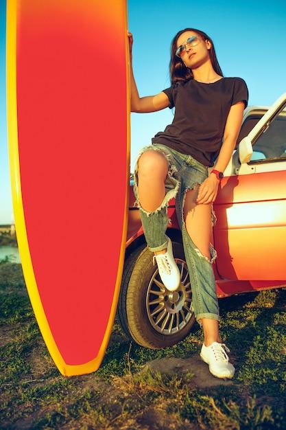 Jonge vrouw zittend op auto met surfplank Gratis Foto