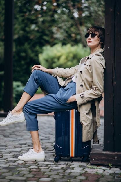 Jonge vrouw zittend op bagage Gratis Foto