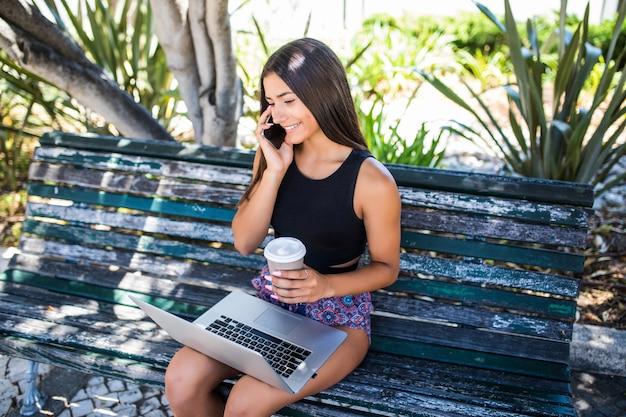 Jonge vrouw zittend op de bank, praten over smartphone, buitenshuis bezig met laptop. Gratis Foto