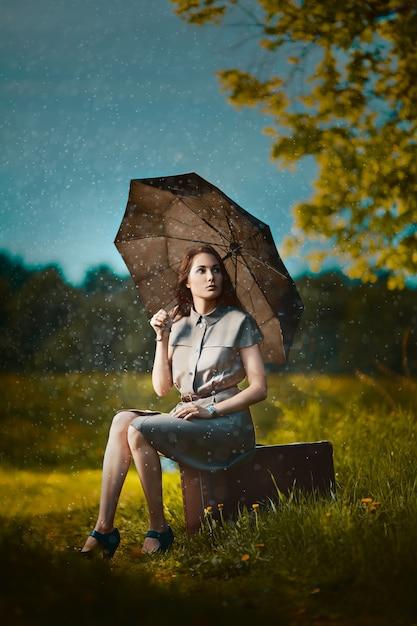 Jonge vrouw zittend op een koffer onder regen en wachten Premium Foto