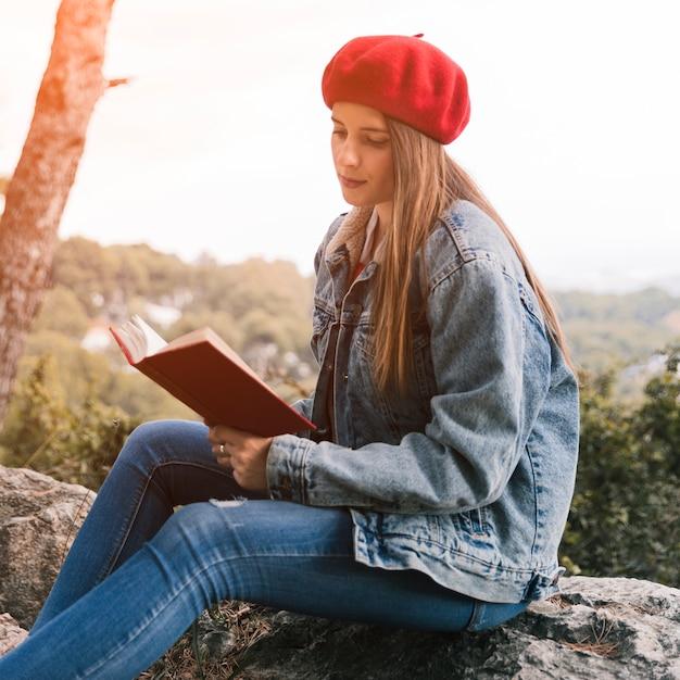 Jonge vrouw zittend op rock leesboek Gratis Foto
