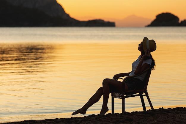 Jonge vrouw zittend op stoel op zonsondergang aan de oever van een meer Gratis Foto