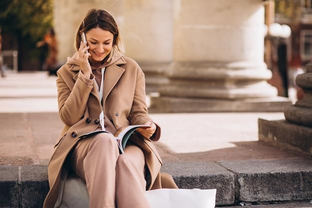 Jonge vrouw zittend op trappen in de stad en het lezen van tijdschriften en praten over de telefoon Gratis Foto