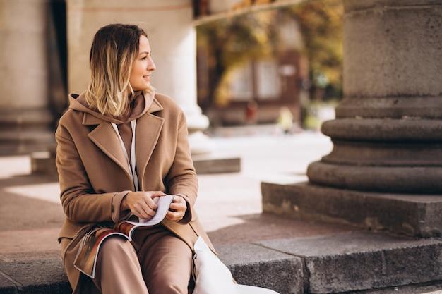 Jonge vrouw zittend op trappen in de stad en het lezen van tijdschriften Gratis Foto