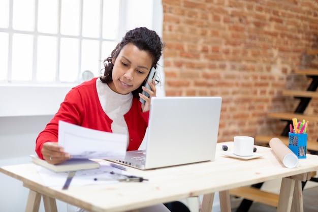 Jonge vrouwelijke architect die aan de telefoon spreekt terwijl hij naar de plannen van een huis kijkt. ruimte voor tekst. thuiskantoor concept. Premium Foto