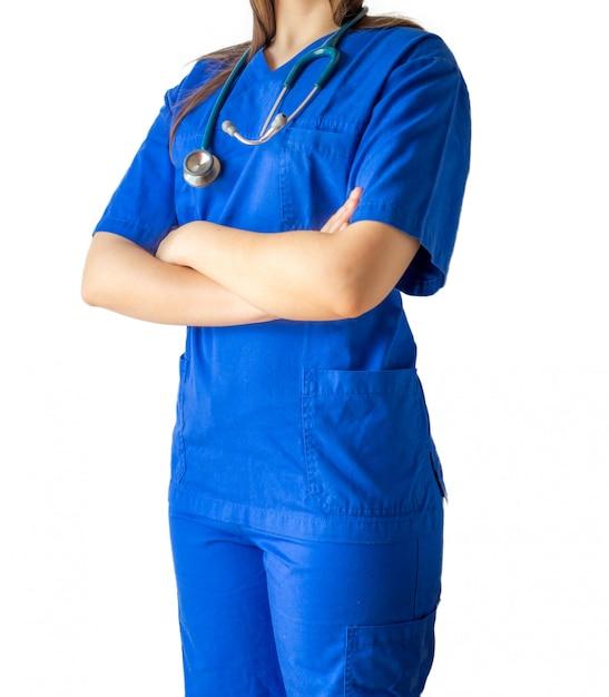 Jonge vrouwelijke arts in een blauw medisch uniform dat zich vol vertrouwen met gekruiste handen bevindt Gratis Foto