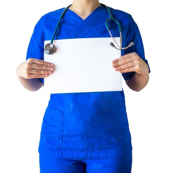 Jonge vrouwelijke arts in een blauw medisch uniform met een leeg witboek met een kopie ruimte Gratis Foto