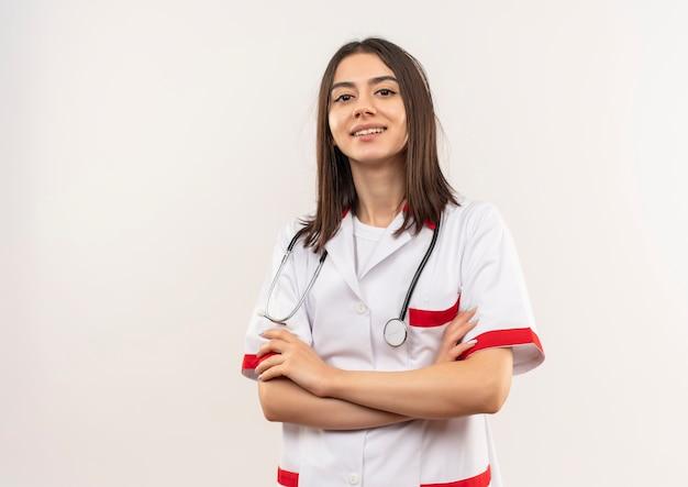 Jonge vrouwelijke arts in witte jas die met een stethoscoop om haar hals naar voren kijkt met hand op borst die zelfverzekerd over witte muur kijkt Gratis Foto