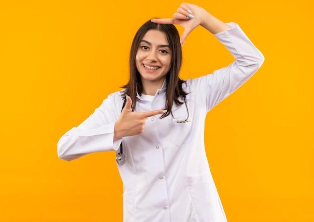 Jonge vrouwelijke arts in witte jas met een stethoscoop om haar nek frame met vingers naar voren kijkend door dit frame glimlachend staande over oranje muur Gratis Foto